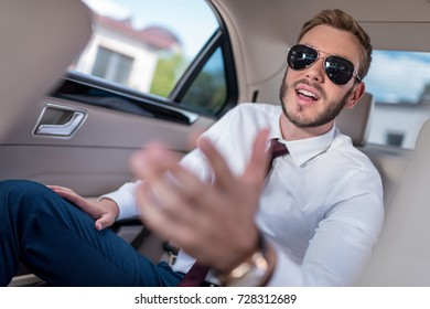 young stylish businessman in sunglasses on backseat of car