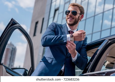 young stylish businessman in sunglasses standing at car
