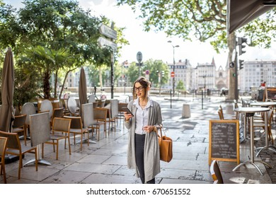 Young stylish businesswoman walking with phone and bag on the street with cafes in Lyon old town