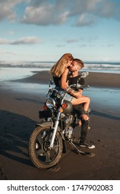 Young, stylish cafe racer couple on vintage custom motorcycle kissing  on the beach