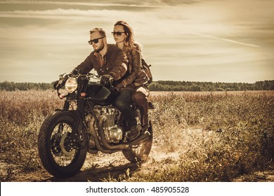 Young, stylish cafe racer couple on the vintage custom motorcycles in a field.