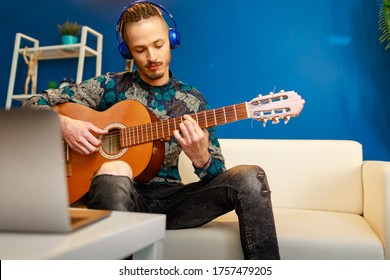 Young stylish caucasian man taking guitar class online at home using his laptop