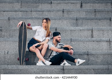 Young stylish couple on concrete stairs with a longboard. Sunny portrait of young stylish couple in the urban city landscape. Image of stylish hipsters couple.