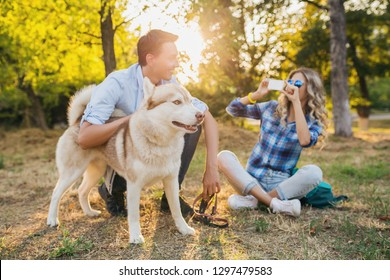 young stylish couple playing with dog in park, man and woman happy family together, husky breed, summer style, sunny, positive romantic mood