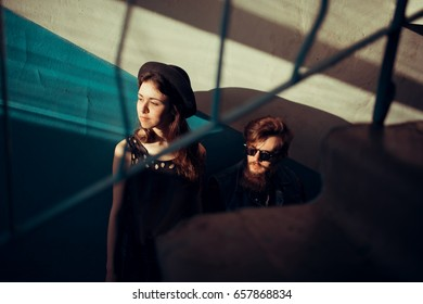 Young stylish couple in the stairwell of the old house at sunset. Teenagers guy and girl in glasses looking out the window. The concept of youth, a date, a walk