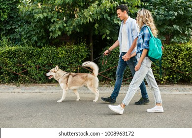 young stylish couple walking with dog in street, man and woman happy together, husky breed, summer season, denim casual style
