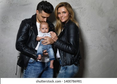 Young and stylish family. Happy mother and father with little baby.