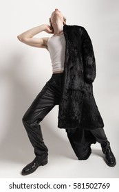 Young stylish fashion man posing in furs and smiling
