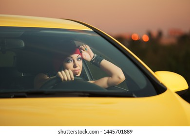 Young stylish fashion woman in red beanie driving a car