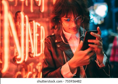 Young stylish female hipster standing near neon red light in night city and listening to music in headphones on modern smartphone. Woman watching media video on cellphone device