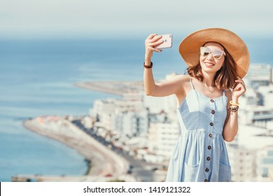 A young stylish girl in a big hat taking selfie near the sea resort town, aerial view