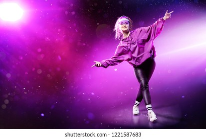 Young stylish girl dancing hip hop on colorful disco background