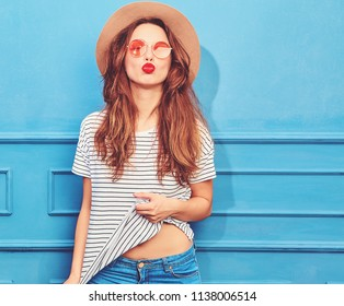 Young stylish girl model in casual summer clothes and brown hat with red lips, posing near blue wall. Giving air kiss