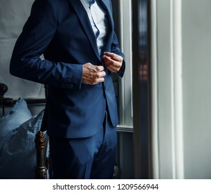 young stylish groom getting ready, blue suit
