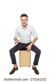 Young stylish guy sitting on the floor and holding a Cajon