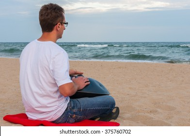 Young stylish guy sitting on the sand beach and playing handpan or hang with sea On Background. The Hang is traditional ethnic drum musical instrument