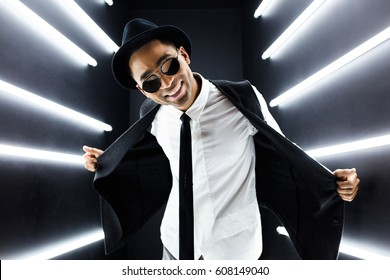 young stylish handsome hipster man, in vintage outfit, retro style, vest, black tie, white shirt, hat, sunglasses, fashion trend, dancing at nightclub party, having fun, positive, emotional, smiling
