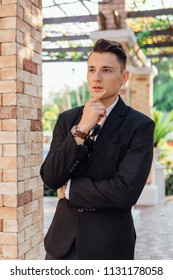Young stylish handsome man posing in modern city park, wearing suit and sunglasses.
