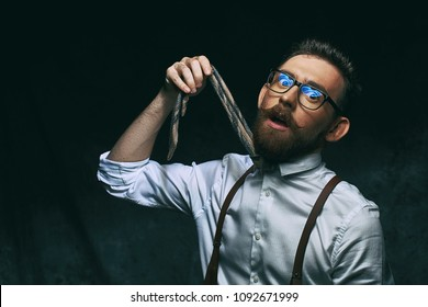 Young stylish hipster businessman or manager holds his necktie in hand as if he decided to hang himself on it conceptually showing high level of stress and overwork.