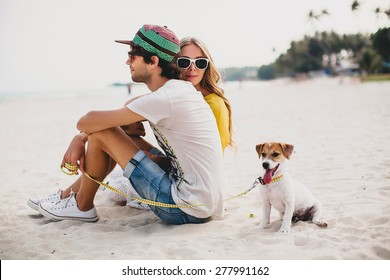 young stylish hipster couple in love walking playing dog puppy jack russell in tropical beach, white sand, cool outfit, romantic mood, having fun, sunny, man woman together? horizontal, vacation