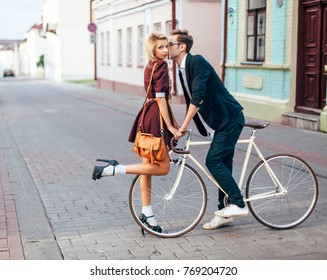 Young stylish hipster couple in love have fun on the street wing vintage bicycle. Beautiful woman kissing her handsome boyfriend.