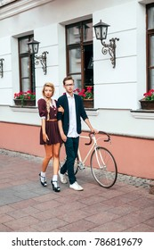 Young stylish hipster couple in love have fun on the street wing vintage bicycle