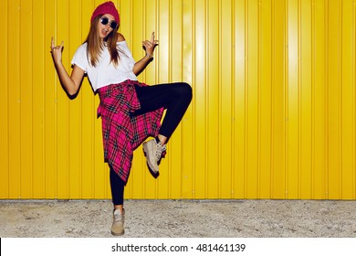 Young stylish hipster  girl having fun   and doing grimaces  near bright yellow urban wall at night with flash. Wearing pink hat, warm hipster boots.