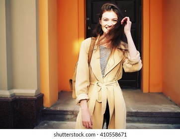 Young stylish hipster girl wearing modern trench coat walking in urban city smiling happy. Caucasian female model in her 20s.