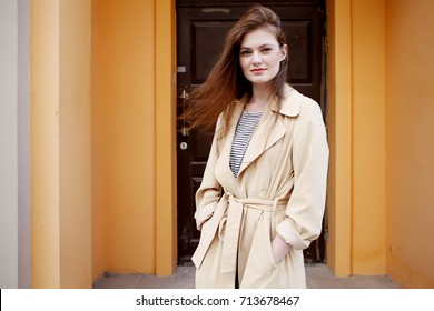 Young stylish hipster girl wearing modern trench coat walking in urban city smiling happy. Caucasian female model in her 20s. Fall fashion