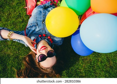 young stylish hipster teen girl happy smiling, park, air balloons birthday party, cool accessories, sunglasses, colorful, sunny, having fun, lying on grass, denim shirt, braces, sunny, from above