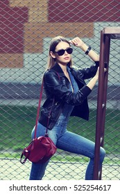 young stylish hipster woman outdoor, wearing sunglasses, black leather jacket, jeans overall, leather backpack, urban fashion