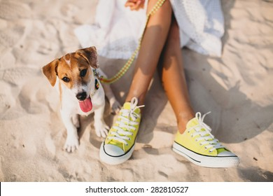 young stylish hipster woman playing dog puppy jack russell in tropical beach, cool outfit, romantic mood, having fun, sunny, horizontal, vacation, lying on the sand, shoes close up