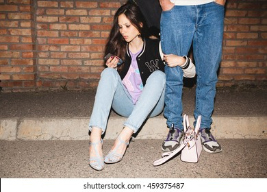 young stylish hipster woman, swag outfit, jeans, embracing men's leg, cool accessories, sitting on ground against brick wall, happy, having fun, looking at smartphone
