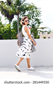 Young stylish hipster woman wearing backpack sunglasses, vintage midi skirt and sneakers, walking on the street at nice sunny summer day, bright fresh colors.