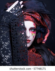 Young stylish lady in black and red silk with creative make-up.