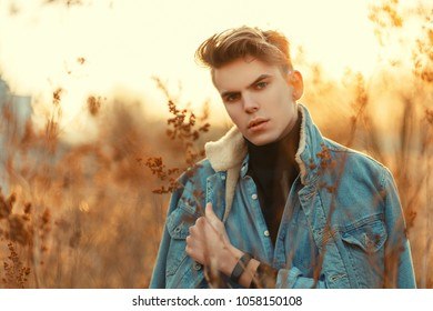 Young stylish male model with haircut in trendy denim clothes on nature at sunset