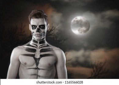 Young stylish man with art grimm for hallowen party. Fashion body art. Face art