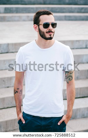 6ca5114ddd70 A young stylish man with a beard in a white T-shirt and glasses.