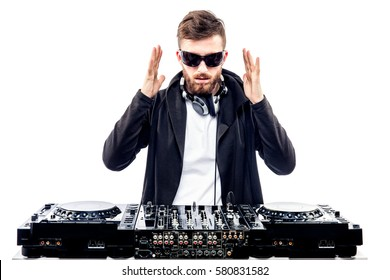 Young stylish man in black sunglasses posing with hands up behind mixing console on white studio background.