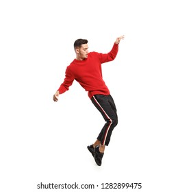 Young stylish man dressed in red turtleneck and dark pants with stripes on the sides dances on the white background in the studio