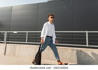Young stylish man hipster in trendy clothes in sunglasses with a black cloth bag in vintage sandals walks is in a city near a gray building. American guy. Fashionable summer menswear. Street style.