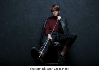 Young stylish man in a jacket in a vintage burgundy golf in trendy jeans and sneakers with a metal chain sits on a chair and looks into the camera in the studio against the black wall. Handsome guy