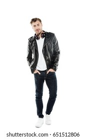 young stylish man in leather jacket with headphones posing isolated on white