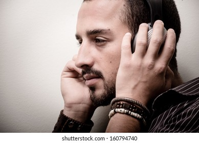 young stylish man listening to music on gray background
