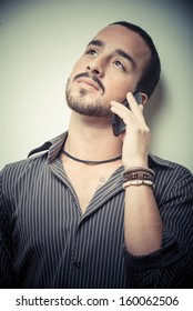 young stylish man on the phone on gray background