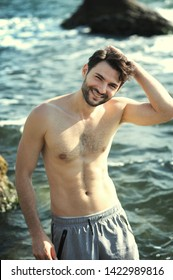 Young stylish man outdoor portrait near the sea, topless