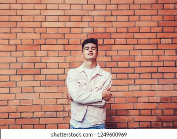 Young stylish man posing with a trendy outfit against a urban background