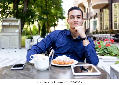 Young stylish man in shirt and jeans sitting in a summer cafe outdoors. Man have a lunch,  smiling and looks into the camera.