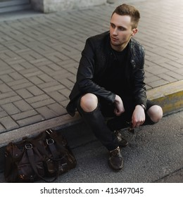 Young stylish man sitting on the street with a bag, life style.