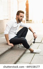 Young stylish man sitting on the street . Streetstyle.